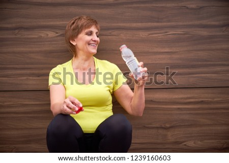 Woman with water bottle smiling. Active mature lifestyle. Lifestyle concept