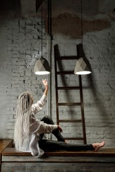 Woman with white braids, in shirt. Young woman sits with raised hand under the light of concrete chandeliers. Mood and emotions, loneliness and sadness.