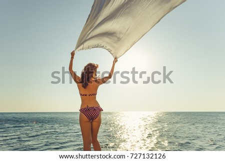Woman with white sarong at beach. Summer portrait of a beautiful girl in bikini walking on the beach. Tropical summer babe lets her pareo blow in the wind.
