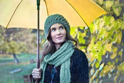 Woman with yellow umbrella smiling as raining