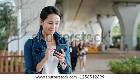 Woman work on smart phone at park