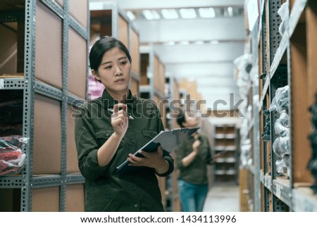 woman worker doing stocktaking of products in cardboard box on shelves in warehouse using clipboard and pen. female staff checking stock in factory stockroom. girl working in storehouse with coworker #1434113996