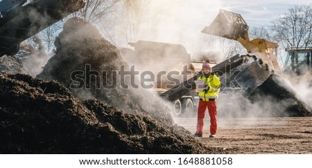 Woman worker standing with clipboard in industrial compost plant Foto stock ©