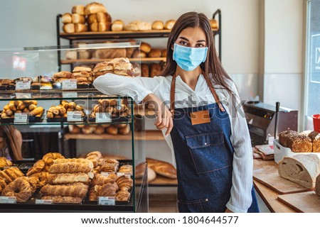 Woman working at a bakery wearing a facemask to avoid the coronavirus. COVID-19 lifestyle concepts. Day in the life of owners of bakery shop with the protocol against the Covid-19 in place.