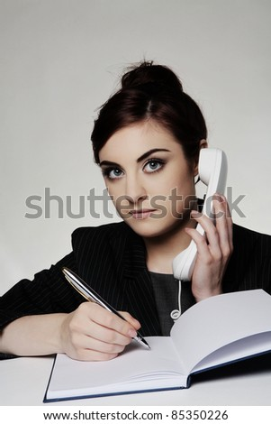 woman working at her desk on her phone