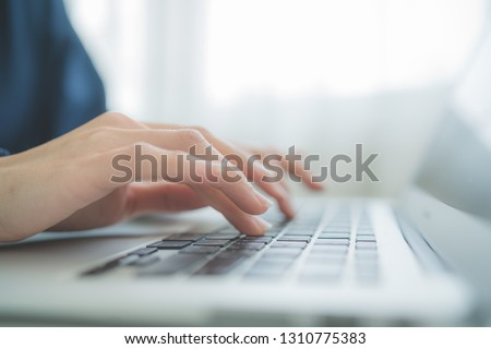 Woman working at home office hand on keyboard close up #1310775383