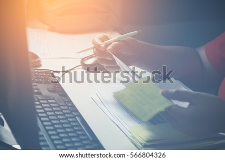 Woman working checking her own business reports on desk until late at night #566804326