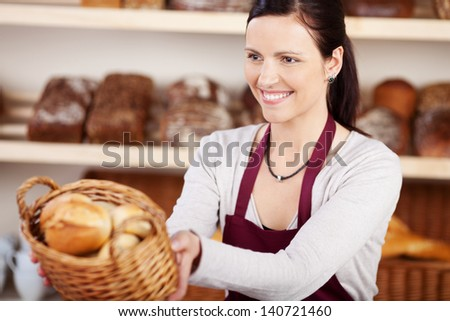 Woman working in a bakery offering a customer a basket of assorted bread and rolls with a friendly smile, focus to the woman