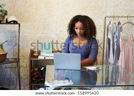 Woman working in clothes shop using laptop, front view