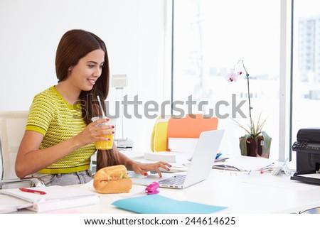 Woman Working In Design Studio Having Lunch At Desk