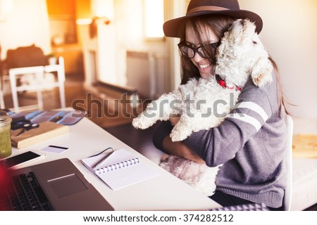 Woman working in her office and hugging her puppy