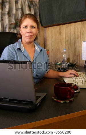 Woman working in home office. Retro style decor, black desk, laptop, coffee and computer.