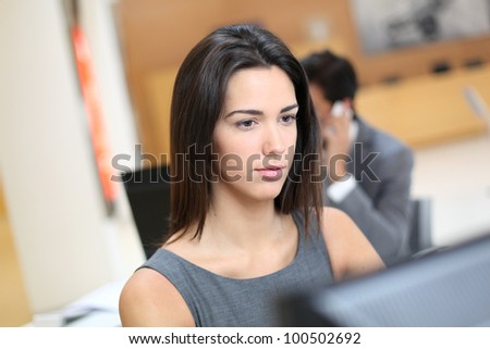 Woman working in office in front of desktop computer