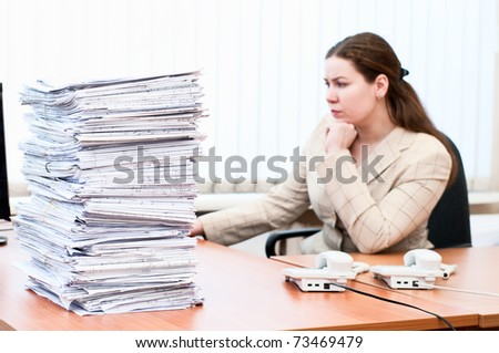 Woman working in office room. Focus on pile of blueprints