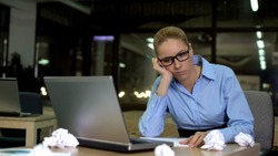 Woman working late in office, feeling tired and lacking ideas, overwork concept