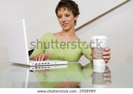 woman working on a computer with a coffee. (focus on coffee)