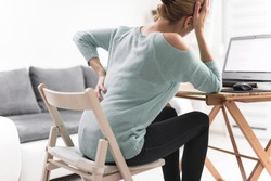 Woman working on a laptop and having headache and back, hip, spine pain.