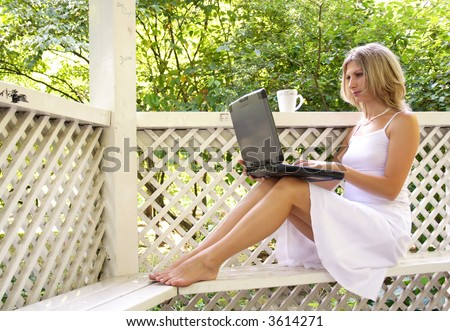 Woman working on computer in the city park and drinking cofee.
