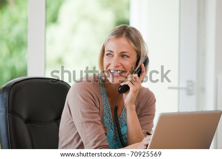 Woman working on her computer while she is phoning at home