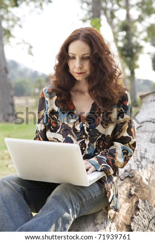 Woman working on her laptop in a park.