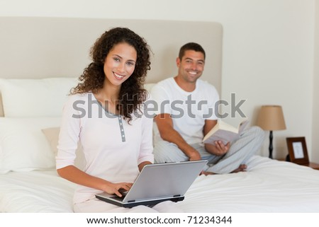 Woman working on her laptop while her husband is reading