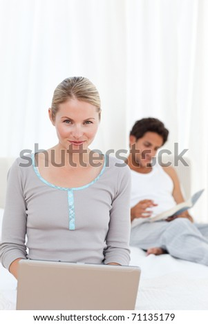 Woman working on her laptop while her husband is reading at home