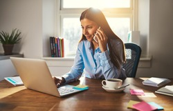 Woman working on laptop at office while talking on phone, backlit warm light