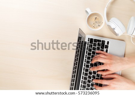 Woman working on laptop. Hands typing on keyboard on office desk.  Top view with copy space