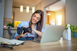 Woman working on laptop in home. Freelance photographer edit photos on computer. Professional photography business. Girl workspace with computer and photo camera. Creative artist lifestyle