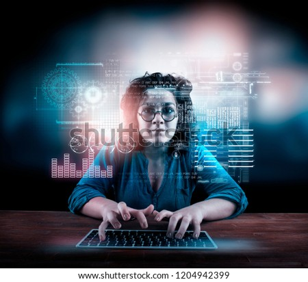 Woman working on laptop with a futuristic infograph interface in front of her #1204942399