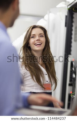 Woman working on servers laughing with colleage in data center