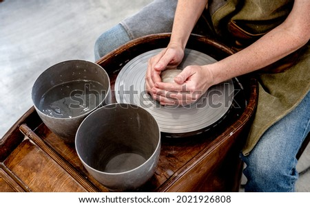 Woman working on the potter's wheel. Ceramist young woman making clay product on pottery lathe in studio. Close up of female hands working on potters wheel Foto stock ©