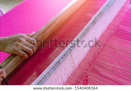Woman working on weaving machine for weave handmade fabric. Textile weaving. Weaving using traditional hand weaving loom on the long cotton strands. Textile production in Thailand. Asian culture. Foto d'archivio ©
