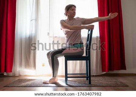 Woman working out doing yoga or pilates exercise using chair. Ardha Matsyendrasana pose variation. ストックフォト ©