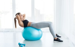 Woman working out with fitness ball in gym, doing exercises for muscle press in white room, copy space