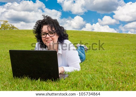 Woman working outdoors in a meadow and looking up from laptop