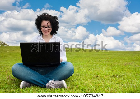 Woman working outdoors in a meadow sitting up with a laptop