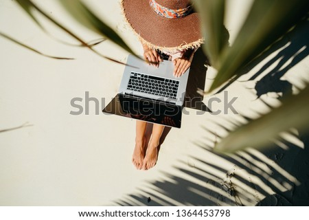 woman working through internet in tropics. Working remotely on the laptop computer through the internet. Working while travelling. top view.