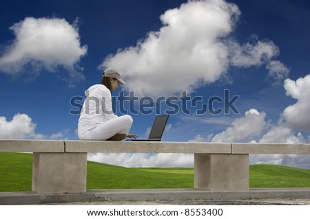 Woman working with a laptop sitting in a wall with a great view over a beautiful green meadow