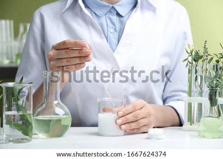 Woman working with cream at table in cosmetic laboratory, closeup