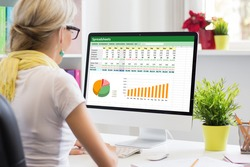 Woman working with data and graphs in spreadsheet document on desktop computer