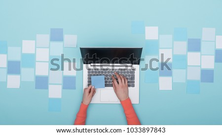 Woman working with her laptop and mosaic of sticky notes, she is holding a sticky note and typing: creativity and planning
