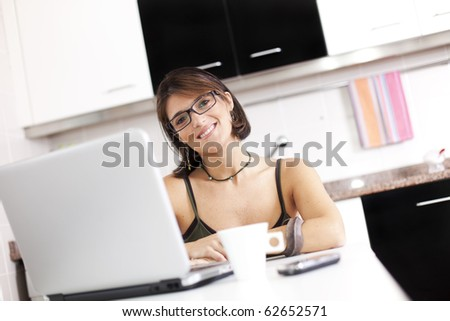 woman working with her laptop while eating her breakfast (selective focus with shallow DOF)