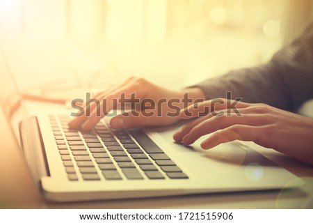 Woman working with laptop at table indoors, closeup