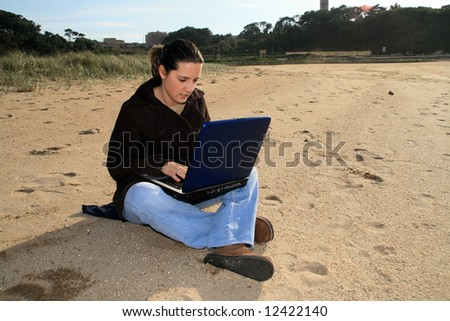 woman working with laptop on the coast - stock photo