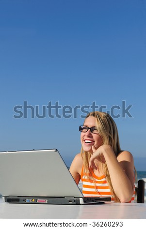 woman working with laptop outdoor against blue sky
