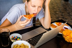 Woman works at the computer and eating fast food. Unhealthy Lifestyle
