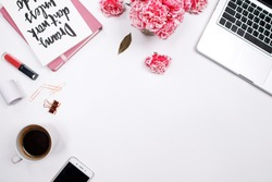 Woman workspace with laptop, handwritten quote notebook, pink carnation flower, smartphone,  lipstick on white background. Flat lay, top view. stylish female blogger concept. spring summer background.
