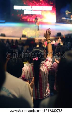 Woman worshipping in Mega Church