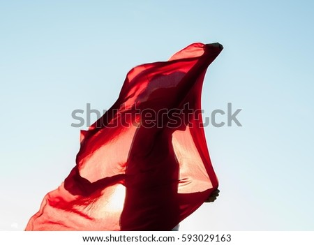 Stock Photo woman wrapped in a red scarf in the wind